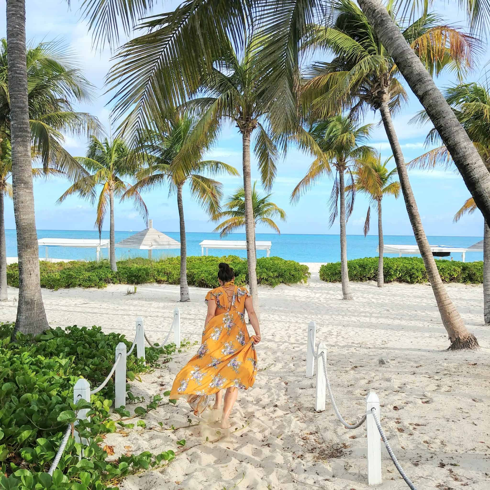Club Med All Inclusive Turks and Caicos Resort running to beach with palm trees in yellow floral dress