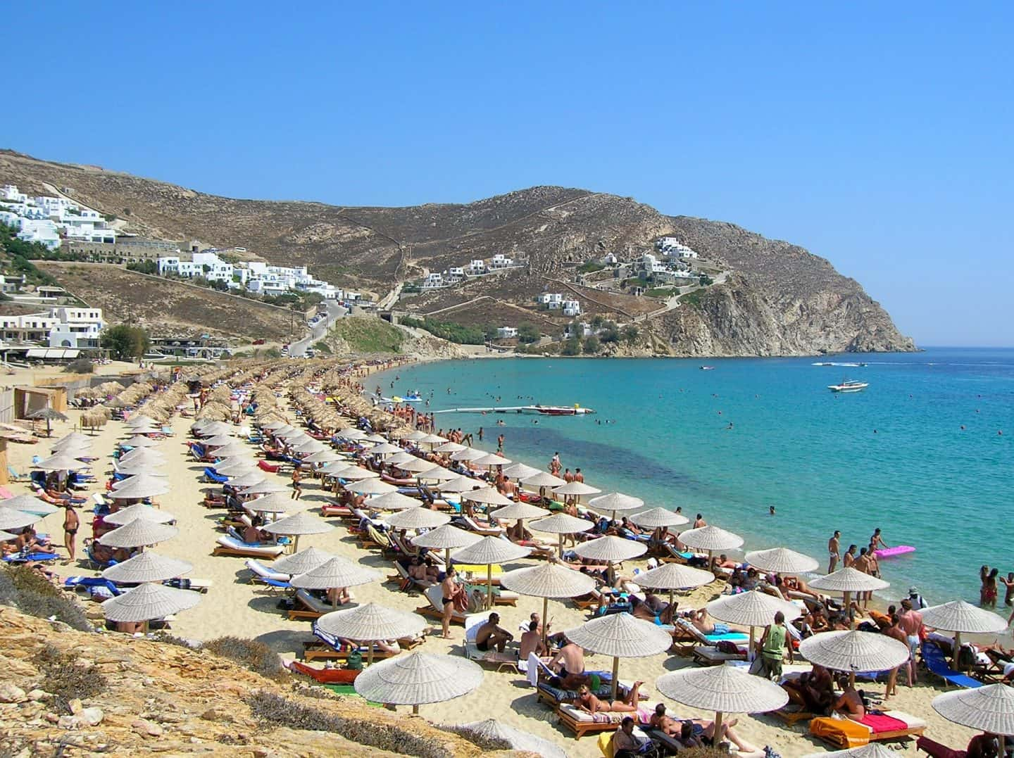 beach lined with beach umbrellas best mykonos beach