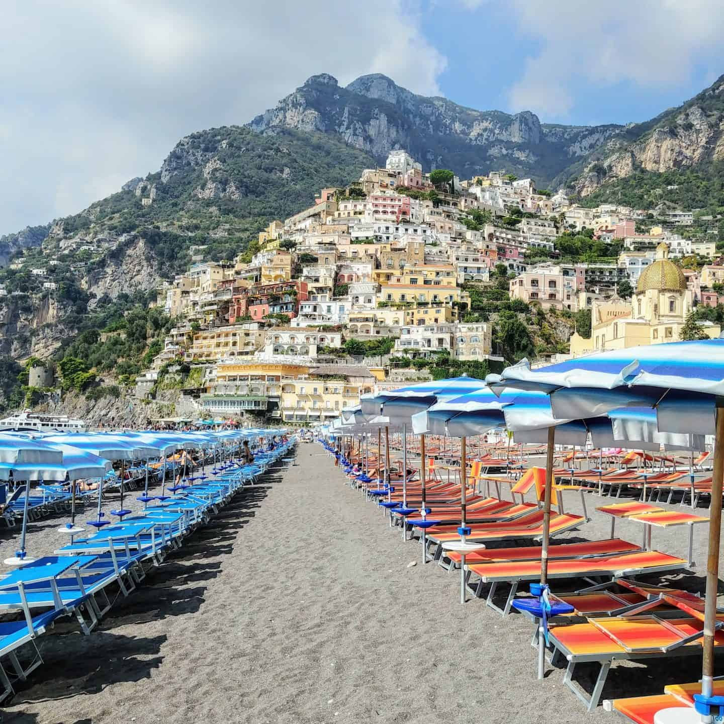 Positano beach lined with beach chairs and umbrellas with mountain view